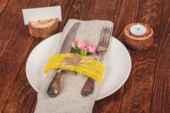 Decorated table for dining in rustic style with pink roses Royalty Free Stock Images