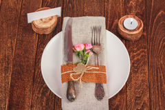 Decorated table for dining in rustic style with pink roses Royalty Free Stock Photo