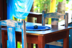 Decorated table outside. Decorated table in the garden. the forniture of old wood painting in blue colors made romantic and exotic mood Stock Photos