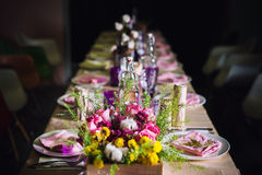 Decorated table ready for dinner. Beautifully decorated table set with flowers, candles, plates and serviettes for wedding or anot Royalty Free Stock Photography