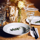 Decorated table ready for dinner. Beautifully decorated table set with flowers, candles, plates and serviettes for wedding or anot Stock Photos