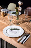 Decorated table ready for dinner. Beautifully decorated table set with flowers, candles, plates and serviettes for wedding or anot Stock Image