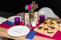 Decorated table ready for dinner. Beautifully decorated table set with flowers, candles, plates and serviettes for wedding or anot Stock Photography