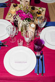 Decorated table ready for dinner. Beautifully decorated table set with flowers, candles, plates and serviettes for wedding or anot Royalty Free Stock Image