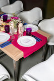 Decorated table ready for dinner. Beautifully decorated table set with flowers, candles, plates and serviettes for wedding or anot Royalty Free Stock Images