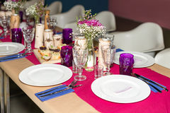 Decorated table ready for dinner. Beautifully decorated table set with flowers, candles, plates and serviettes for wedding or anot Stock Photo