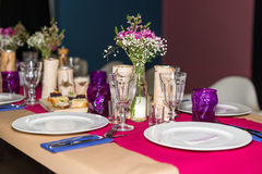 Decorated table ready for dinner. Beautifully decorated table set with flowers, candles, plates and serviettes for wedding or anot Royalty Free Stock Photo