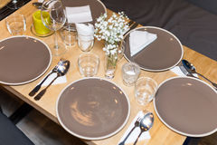 Decorated table ready for dinner. Beautifully decorated table set with flowers, candles, plates and serviettes for wedding or anot Royalty Free Stock Photos