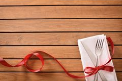 Decorated table with red ribbon for special event top. Table decorated with red ribbon for special event and planked wood table background. Top view Royalty Free Stock Images
