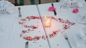 Decorated table for a romantic meeting. Table with the restaurant is festively decorated with petals and a candle. panorama of the camera on the table stock video