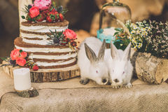 Decorated table for two decorated with floral composition wood background with 2 rabbits Royalty Free Stock Photos