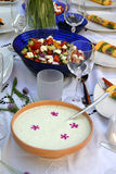 Decorated table with tzatziki and colorful salad. A nicely decorated table with wedding glasses and colorful salad with tomatoes and feta cheese Royalty Free Stock Images