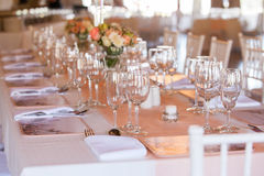 Decorated table at wedding reception. Table at wedding reception decorated with flowers, candles and set with cutlery and crockery Stock Photo