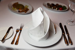 Decorated table with white tablecloth. Photo of decorated table with white tablecloth and napkin Stock Image