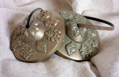 Decorated Tibetan Tingsha Cymbals on Hessian Fabric. A pair of Tibetan Tingsha cymbals, with symbol patterns, on hessian fabric. Themes: methods of meditation stock photos