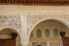 Decorated tiles and columns with geometric shapes and colors in the Alhambra. Detailed view of tiles and columns with geometric shapes in various colors Royalty Free Stock Photo