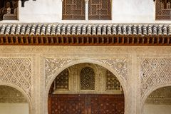 Decorated tiles and columns with geometric shapes and colors in the Alhambra, Spain. Detailed view of tiles, arch and columns with geometric shapes in various Royalty Free Stock Photo