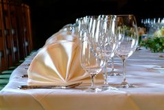 Decorated tish. Many glasses and yellow napkins on decorated table Royalty Free Stock Image
