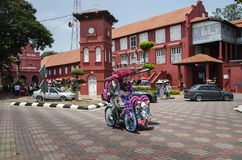 Decorated trishaw with colorful flowers and doll for hire at Malacca city, Malaysia Royalty Free Stock Image