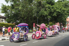 Decorated trishaw with colorful flowers and doll for hire at Malacca city, Malaysia Stock Photos
