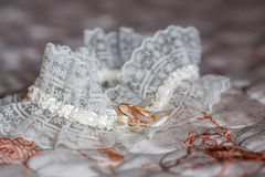 Decorated wedding garter with two golden rings. Marriage concept Royalty Free Stock Images