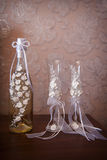 Decorated wedding glasses and bottle of champagne Royalty Free Stock Photos