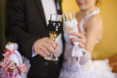 Decorated wedding glasses in the hands of the bride and groom Stock Image