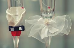 Decorated wedding glasses. Two wedding glasses decorated in the style of the bride and groom Stock Images