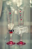 Decorated wedding glasses. Two wedding glasses decorated in the style of the bride and groom Royalty Free Stock Photos