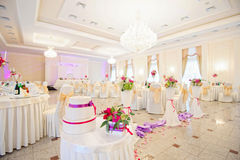 Decorated wedding restaurant in white colors with flowers Stock Photos