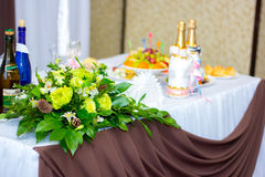 The decorated wedding table for newlyweds. The wedding table decorated in flowers for newlyweds Royalty Free Stock Photos