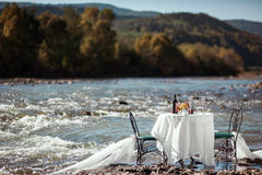Decorated wedding table on the river Stock Photos