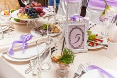 Served wedding table. A decorated wedding table with a seat number five. Served wedding table Royalty Free Stock Images