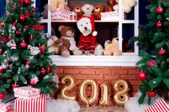 Christmas Dog as symbol of new year. Decorated west highland white terrier dog as symbol of 2018 New Year in red sweater sitting on shelf with teddy bears in Stock Image
