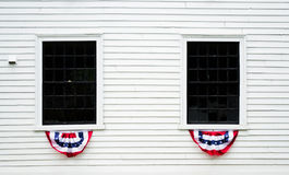 Decorated windows on a white colonial building in New England Royalty Free Stock Photo