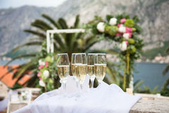 Decorated wineglasses with champagne are on wedding ceremony near wedding arch, mountains, sea, palm. stock photos