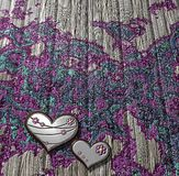 Decorated wooden board with metallic hearts Stock Photos