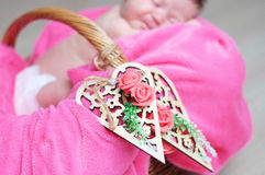 Decorated wooden hearts on basket on focus, newborn baby girl sleeping in basket, lying in pink blanket, cute child. Daughter announcement card Stock Photography