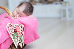 Decorated wooden hearts on basket on focus, newborn baby girl sleeping in basket, lying in pink blanket, cute child, daughter Stock Photography
