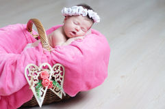 Decorated wooden hearts on basket on focus, newborn baby girl sleeping in basket, lying in pink blanket, cute child Stock Photography