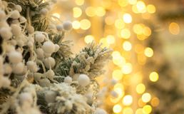 Christmas tree with fake snow and blurred lights at the back. Decorated xmas tree and blurred lights Stock Image