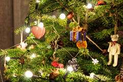Decorated xmas tree. Gift with bow. Macro photography of xmas tree. Lights on tree. Stock Images