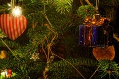 Decorated xmas tree. Gift with bow. Macro photography of xmas tree. Lights on tree. Royalty Free Stock Photo