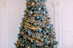 Decorated xmas tree on white wall background. Close up royalty free stock images