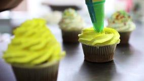 Decoratie die van chocolade cupcake met geel suikerglazuur, veelkleurige cupcakes voor de partij van de jonge geitjesverjaardag m stock videobeelden