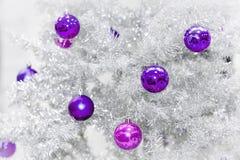 Decoratie ultraviolette snuisterijen op zilveren kunstmatige Kerstboom Royalty-vrije Stock Afbeeldingen