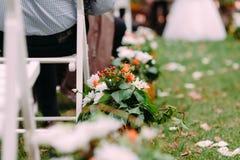 Decoratie van witte en oranje bloemen met groene bladerendecoratie Openlucht huwelijksceremonie stock afbeeldingen