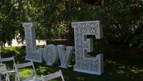 Decoratie voor de huwelijksceremonie, een reusachtige inschrijvingsliefde stock video