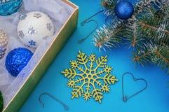Decoratie voor Kerstmis in een doos, een sneeuwvlok, een boom en haken Stock Afbeeldingen