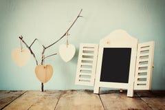 Decoratief bordkader en houten hangende harten over houten lijst klaar voor tekst of model retro gefiltreerd beeld royalty-vrije stock afbeelding